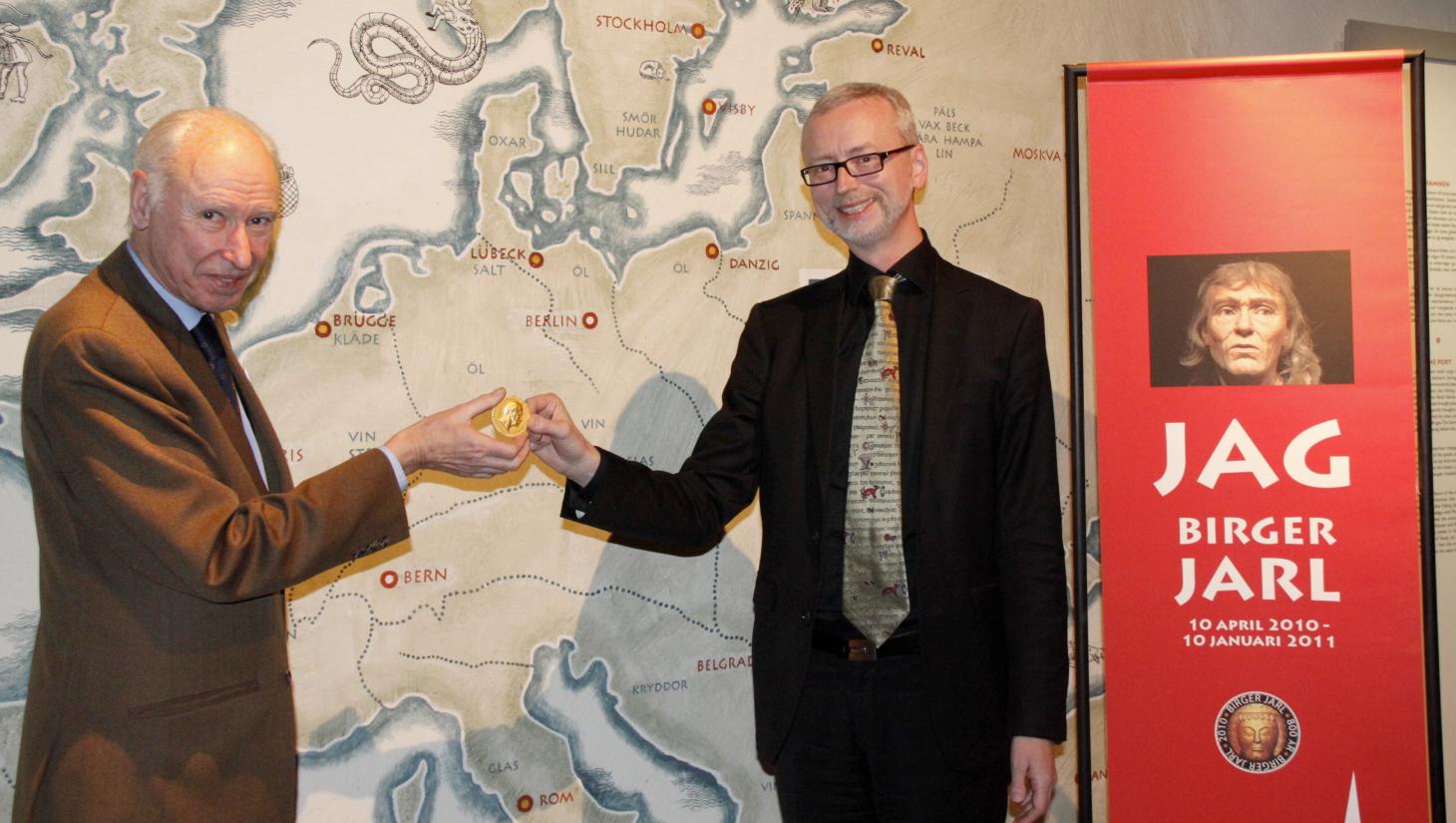Svenska Fornminnesföreningens ordförande Jan Svanberg överräcker Monteliusmedaljen till Dick Harrison. Foto: Boris Söderlind.